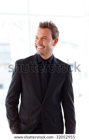 Isolated smiling handsome businessman in office