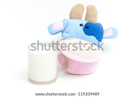 Isolated soft hand puppet cow with glass of milk