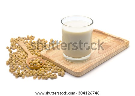 Isolated soy beans and soy milk in a glass on wooden tray - stock photo