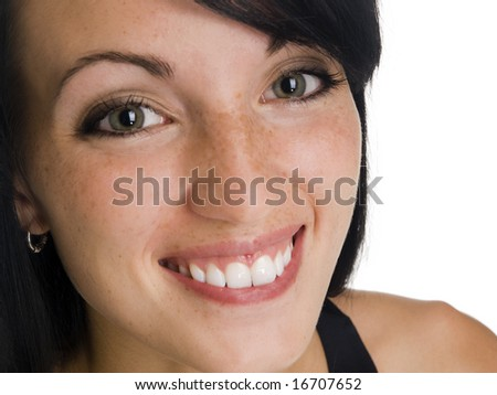 Isolated studio headshot of a businesswoman smiling while looking at the camera.