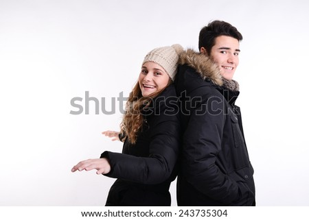 isolated studio portrait of a happy young couple in winter outfit