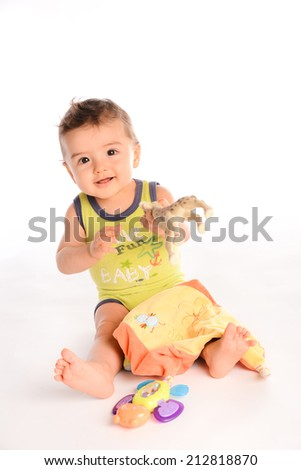 isolated studio portrait of lovely toddler baby boy playing and laughing