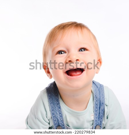 isolated studio portrait on white background of a lovely toddler baby boy playing and laughing