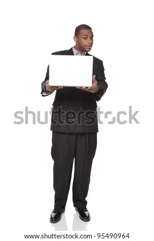 Isolated studio shot of an African American businessman standing and looking warily at a laptop comptuer he is holding out in his hands. - stock photo