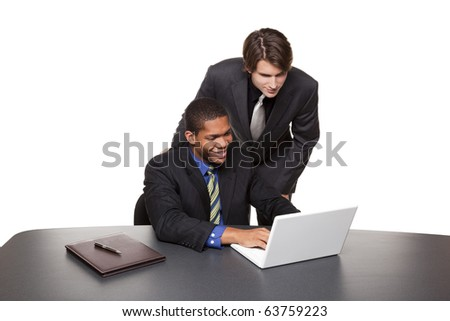 Isolated studio shot of two happy businessmen working on a laptop at a conference table. - stock photo
