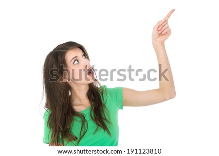Isolated surprised young woman is pointing with index finger over withe background.  - stock photo