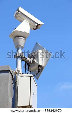isolated Surveillance Security Camera or CCTV on blue sky, left perspective