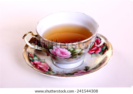 Isolated tea cup with tea against a white backdrop. - stock photo