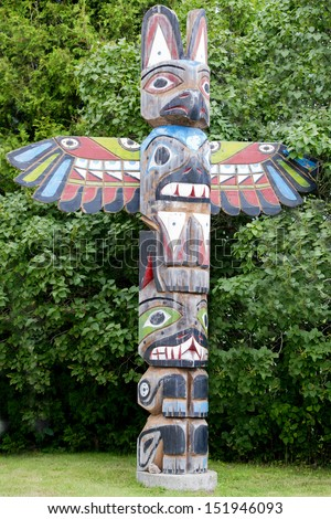 Isolated totem wood pole in the green forest background