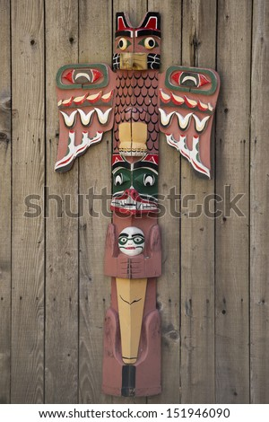 Isolated totem wood pole in the wood background - stock photo