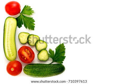 Isolated vegetables tomato cucumber and parsley leaves.