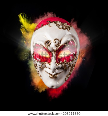 Isolated Venice mask with freeze motion of colored powder on black background - stock photo