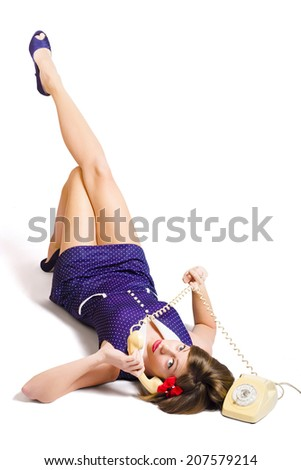 Isolated vertical photograph of a charming pin up model talking on telephone while twirling cord on studio white background - stock photo