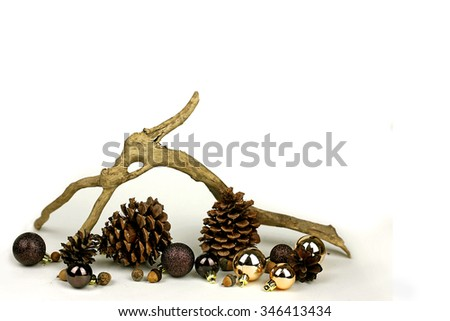 Isolated weathered driftwood, acorns, and pine cones, with gold and brown Christmas Tree decorations frame a white background for Copy-space. - stock photo