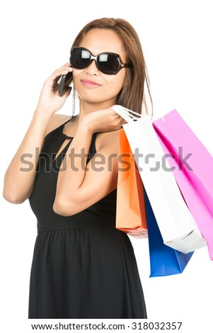 Isolated white background of a beautiful, hip, fashionable Asian shopper wearing an elegant black dress and sunglasses while talking on a mobile phone holding department store bags