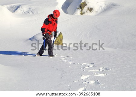 Isolated woman carrying ice axes on snowy trail - stock photo