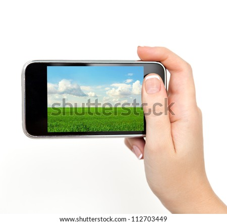 isolated woman hand holding the phone tablet touch computer gadget with the image of green grass and blue sky field