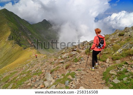 Isolated woman hiking on mountain trail above the clouds - stock photo