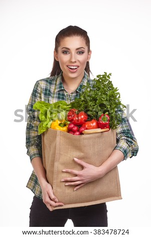 Isolated woman holding a shopping bag full of vegetables