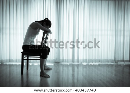 Isolated woman sitting on a chair feeling upset and sad. - stock photo