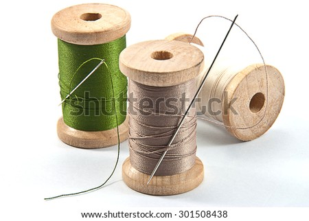 Isolated wooden spool of thread and needle - stock photo