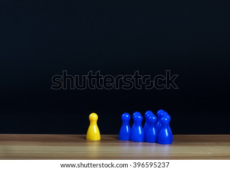 isolated yellow pawn and group of blue pawns on a table
