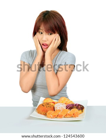 Isolated young asian woman with a donuts on the table