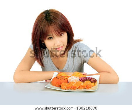 Isolated young asian woman with a donuts on the table - stock photo