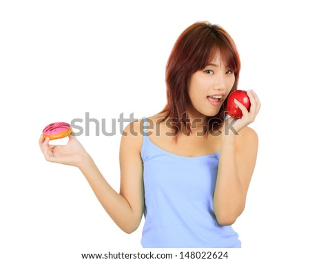 Isolated young asian woman with an apple and a piece of donut - stock photo
