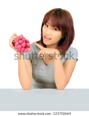Isolated young asian woman with grapes over white.