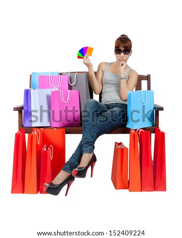 Isolated young asian woman with shopping bags and credit cards - stock photo