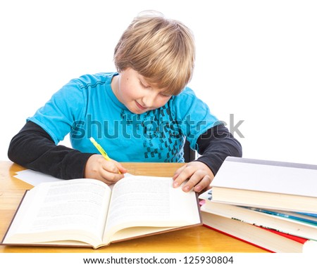 isolated young boy at a table doing homework with books. Space for custom text