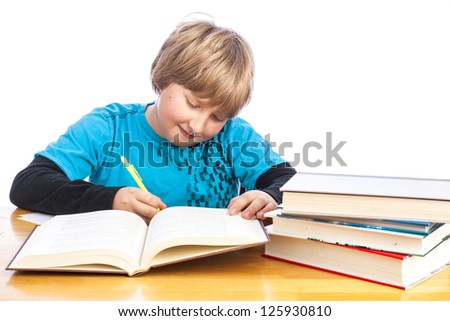 isolated young boy at a table doing homework with books. Space for custom text - stock photo