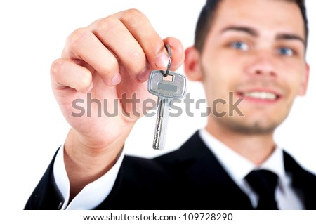 Isolated young business man giving key