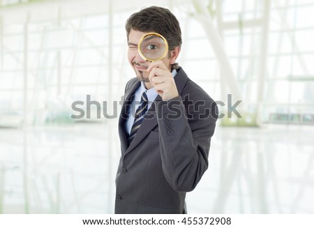 Isolated young business man with magnifying glass, at the office - stock photo