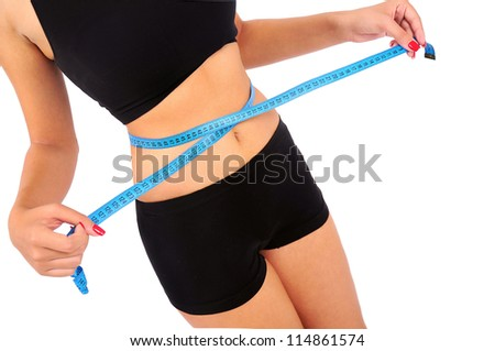 Isolated young fitness woman measuring - stock photo
