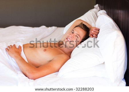 Isolated young man relaxing in bed