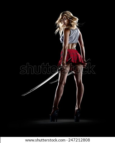 Isolated young sexy girl is standing with the swords - stock photo