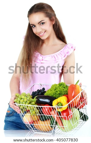 Isolated young woman holding basket of vegetables on light background