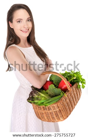Isolated young woman holding basket of vegetables on white background