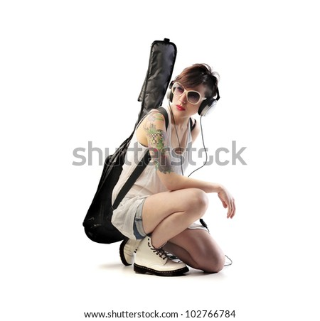 Isolated young woman wearing headphones and carrying a guitar case on her shoulders - stock photo