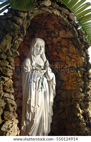 Israel, Christmas picture, a miniature sculpture of the Madonna of the Rocks, standing in the courtyard of the monastery under a palm tree