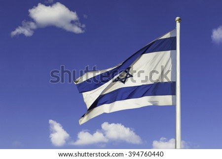 Israel flag flapping in the wind isolated against the blue sky. The flag is on a pole and flapping to the left. there are white clouds in the sky