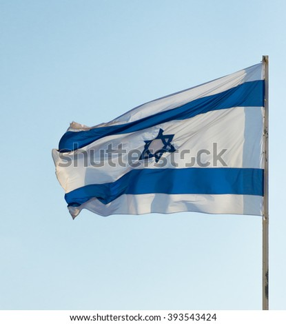 Israel flag flapping in the wind isolated against the sky. The flag is on a pole and flapping to the left - stock photo