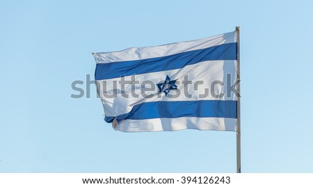 Israel flag flapping in the wind isolated against the sky. The flag is on a pole and flapping to the left