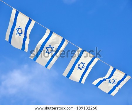 Israel flags in a chain in white and blue showing the Star of David hanging proudly for Israel's Independence Day (Yom Haatzmaut) - stock photo
