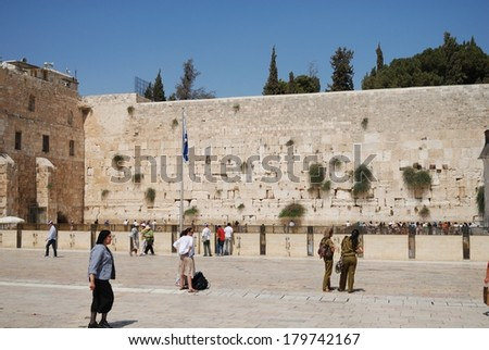 ISRAEL, JERUSALEM - JULY 7, 2010: People are approaching The Western Wall during daytime. It's located in the Old City of Jerusalem at the foot of the western side of the Temple Mount.