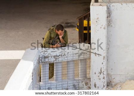 ISRAEL, ROSZ HA-NIKRA- SEPTEMBER 18, 2014: A soldier of the Israeli Defense Forces patrols  September 18, 2014 in Rosz ha-Nikra. - stock photo