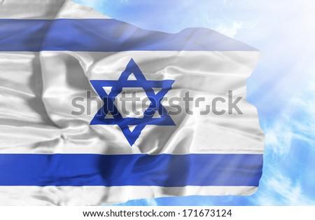 Israel waving flag against blue sky with sunrays - stock photo