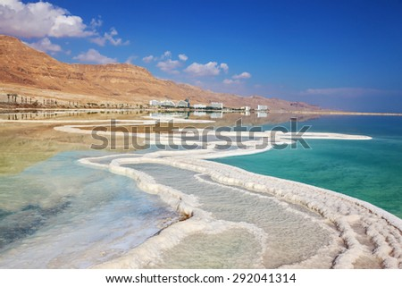 Israeli coast of the Dead Sea. Path from the salt winds picturesquely in salt water. Hotels on the bank are reflected in smooth water - stock photo